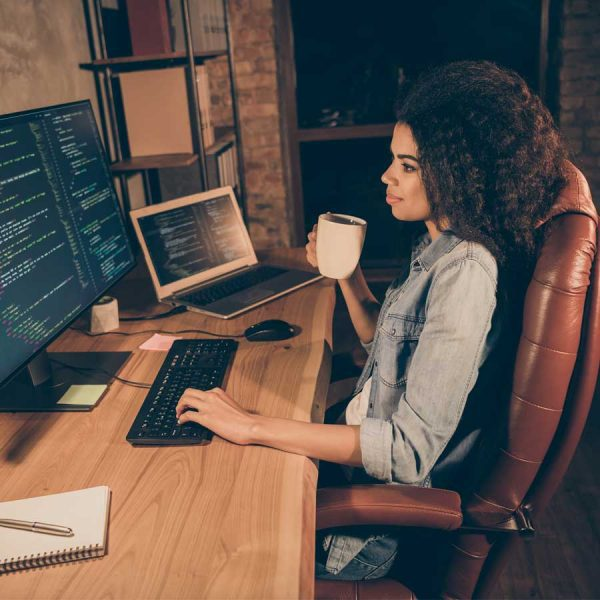 female passively searching for jobs at desk coding at night
