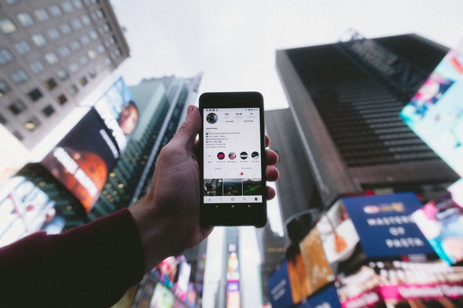 hand holding phone with instagram featured up in the sky in times scare