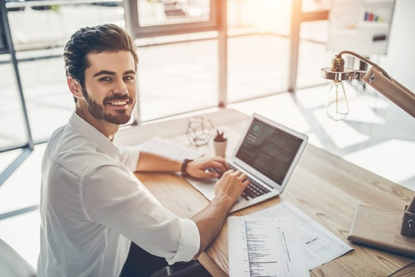 man working on resume at desk at home and smiling at camera