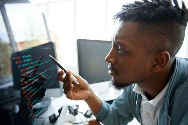 african american man learning upskilling looking confused at computer as he codes