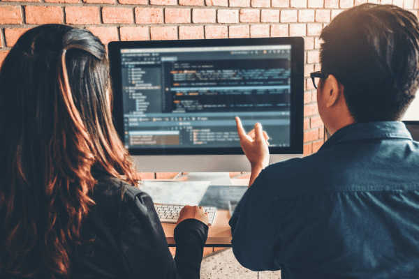 man and woman confused at coding proving the need for upskilling and reskilling