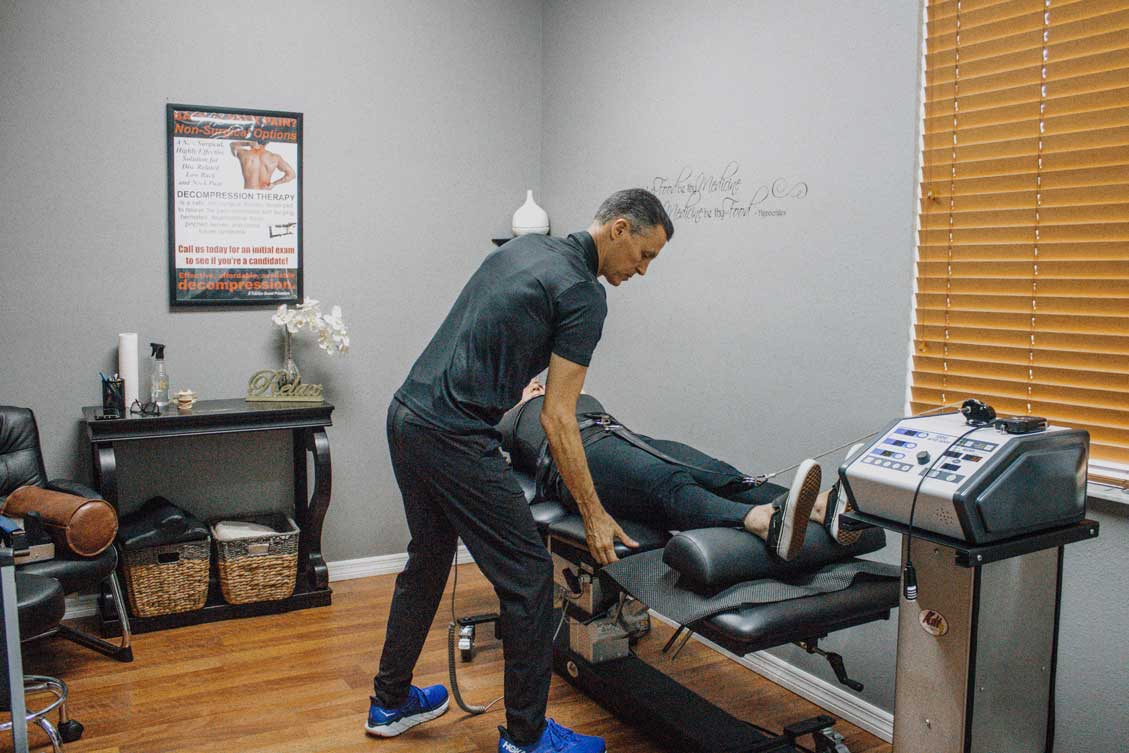 patient experiencing benefits of spinal decompression while top chiropractor adjusts machine