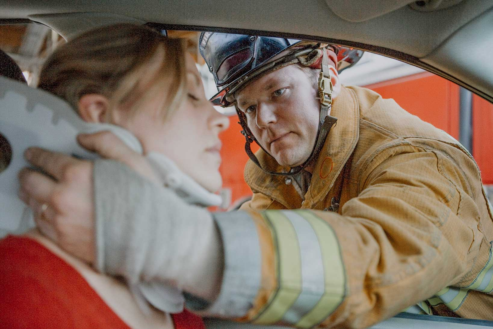 woman needing chiropractic adjustment after car accident in car with fire fighter help